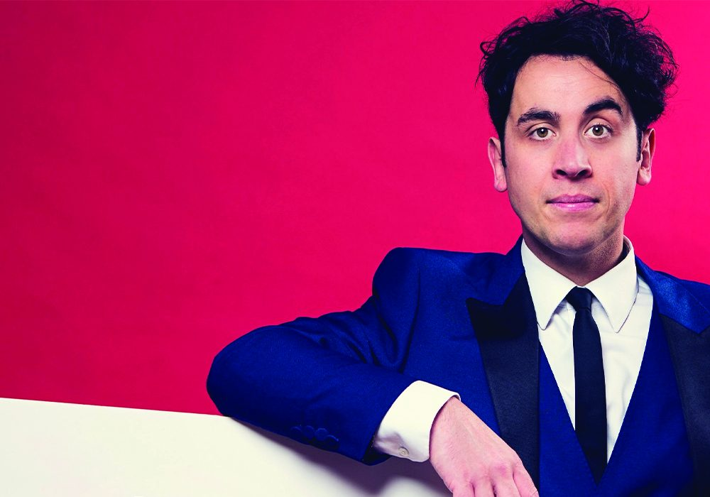 Pete friman standing in front of a red background