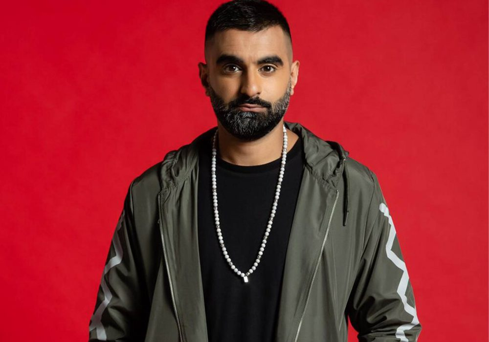 Tez Ilyas looking towards camera wearing green jacket on red background