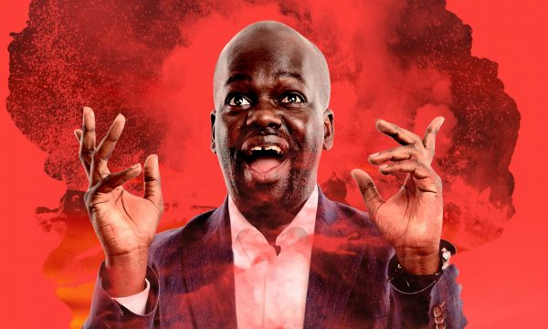 Daliso Chaponda stands in a mushroom cloud on a red background, he's pulling a silly face