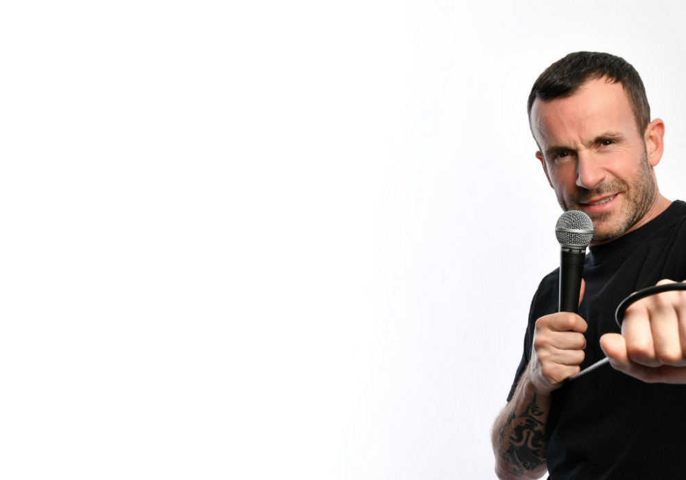 Comedian Gary Meikle (short dark hair and tattooed arms in a black t-shirt) holds a microphone in a cheeky pose