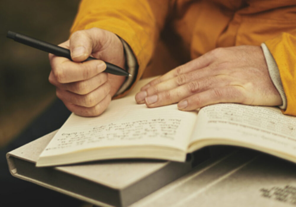 A person sits writing in an open notebook