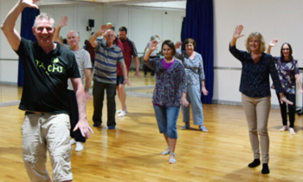A group of people doing a tai chi pose, they are all smiling.