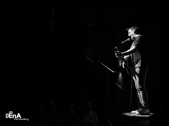 Black and white of a man standing on stage with a viold