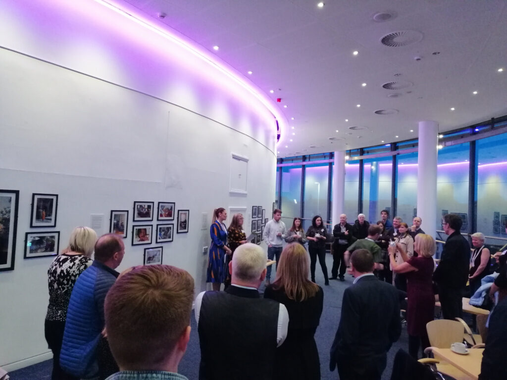 A crowd of people gathered in a gallery to view artwork lining the walls