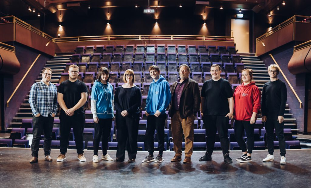 A group of people stand on a stage with rows of empty theatre seats behind them.