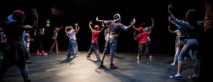 A group of young people practcising street dance on stage