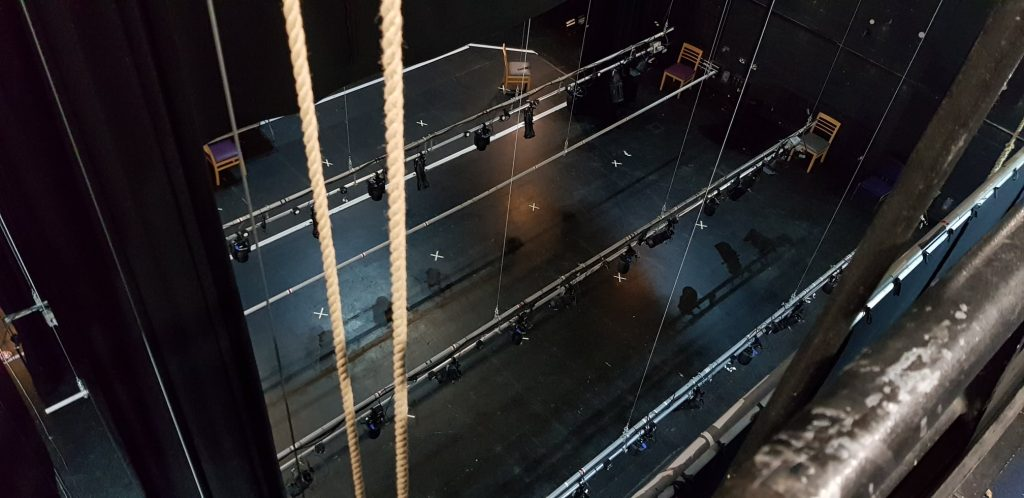 lightings bars suspended on ropes above a black stage