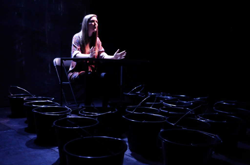 Holly Gallagher sits behind a table, surrounded by buckets. Her hands are slightly raised in the air and she looks like she's speaking to an audience.