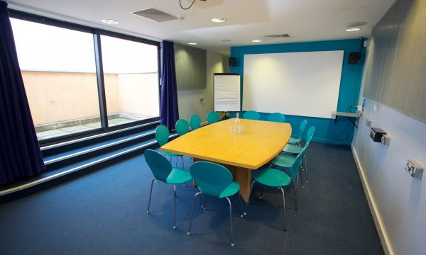 Meeting room with a large boardroom table surrounded by chairs