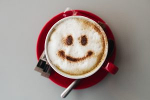 A frothy coffee with a smiley face made in chocolate powder