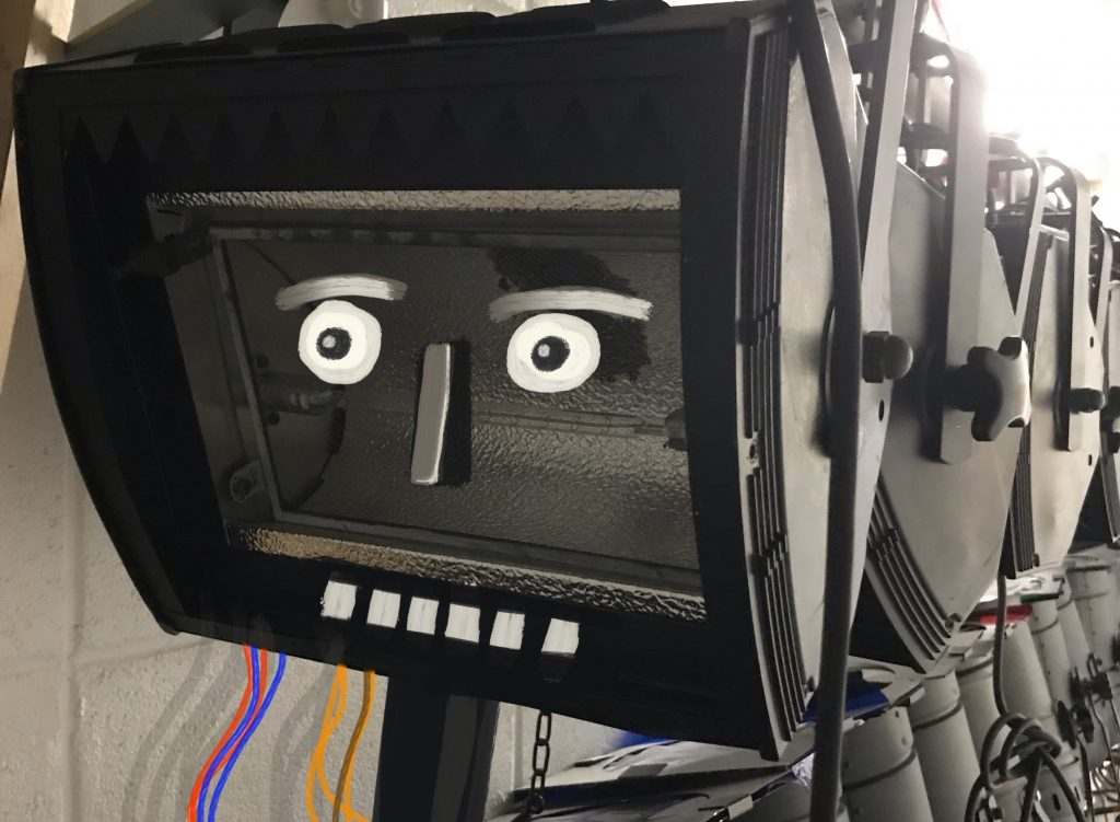A theatre light with a surprised face painted in