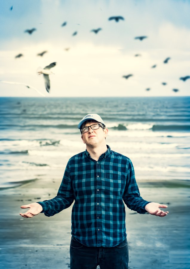 Mike Edwards standing a beach surrounded by seagulls