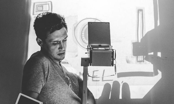 Black and white image of Scott Turnbull sitting behind an overhead projector. An illustration he;s creating is projected onto a screen behind him.