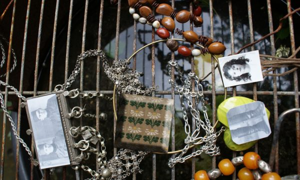 A selection of beads, other jewellery and photographs (of people) lie on a metal grille over water.