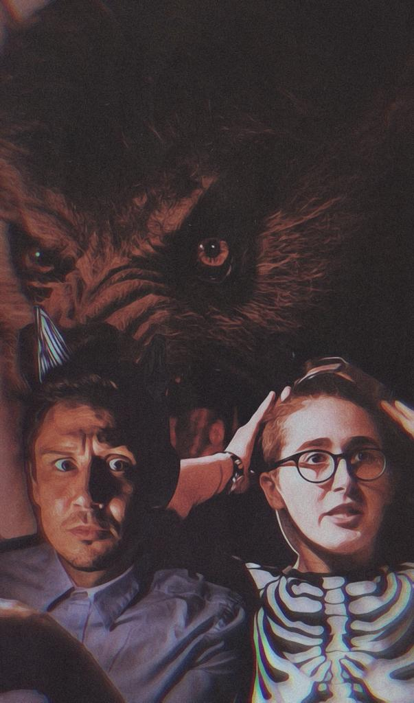Scott Turnbull and Melody Sproates with the image of a vicious looking wolf behind them in the background