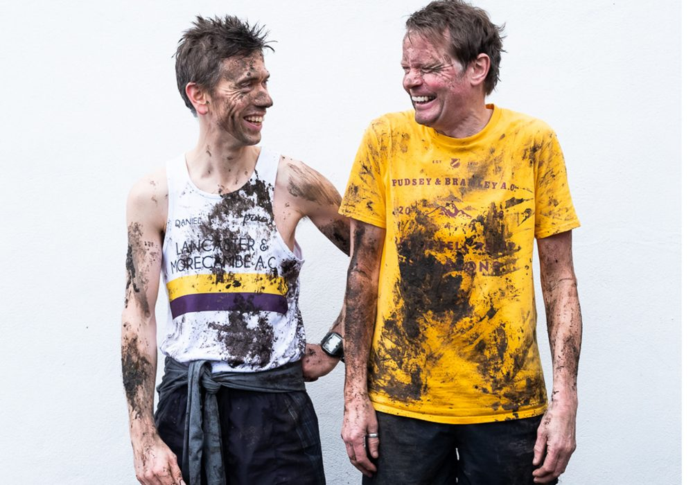 Daniel Bye and Boff Whalley in running attire. They are laughing and covered in mud.