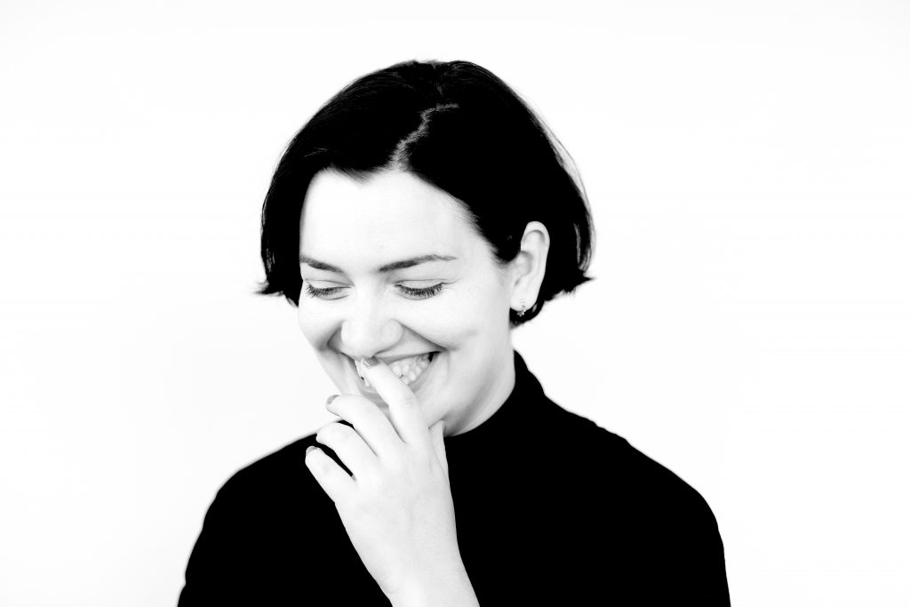 Black and white headshot of Lauren Vevers. Lauren is looking downwards and smiling, and has one hand to her mouth.