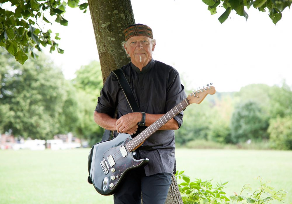 Image of Martin Barre leaning against a tree. He is holding a guitar.