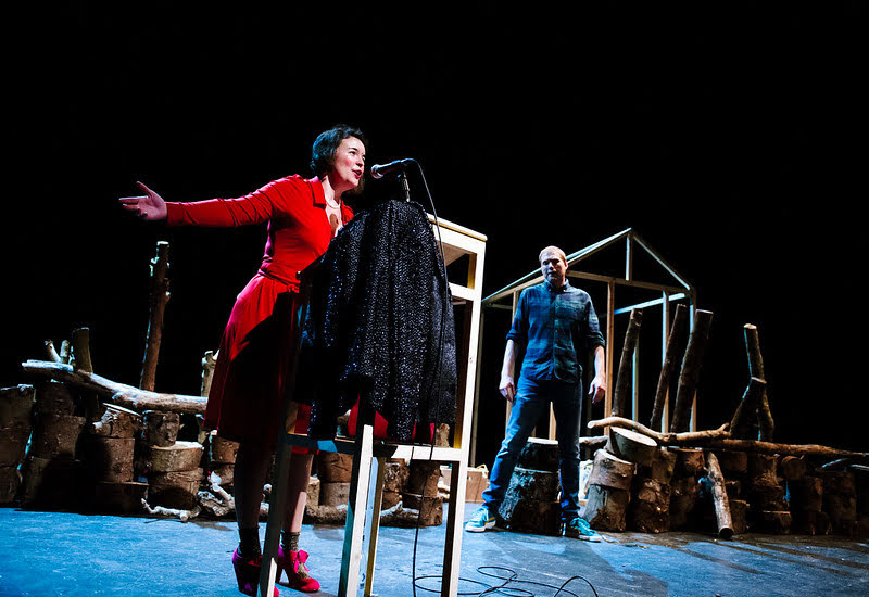 A man and a woman on stage. The woman is wearing a red dress and speaking animatedly at a podium. The man stands further back in jeans and a checked shirt, and is surrounded by wooden structures he's been building while she speaks.