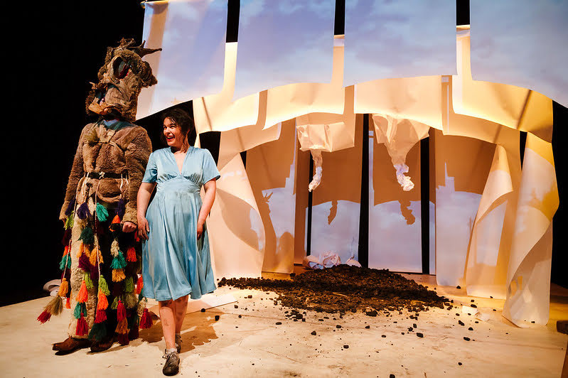A man and woman stand on stage in front of a set created from paper and coal. The woman is wearing a sky blue dress and the man is dressed in costume.
