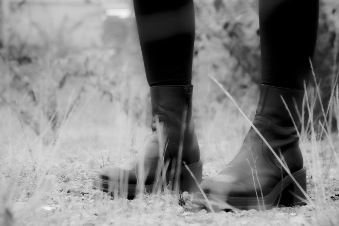 A black and white image of a person's lower legs and feet (wearing black boots).