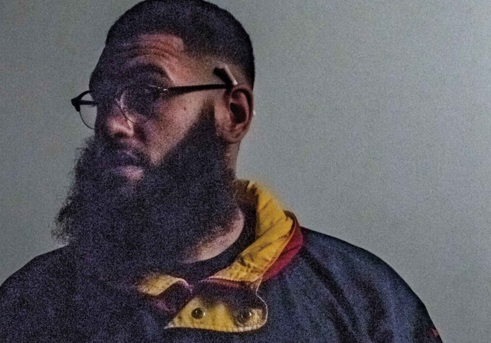 Jamali Maddix has a cigarette tucked behind his ear. He's looking off to one side.