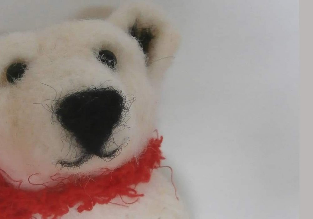 A felt polar bear wearing a red scarf, on a white background