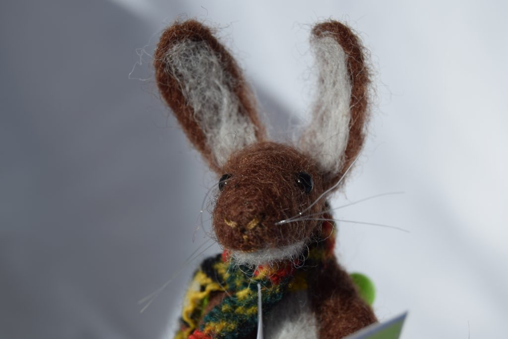 A felt brown hare, wearing a multicoloured scarf, on a white background.
