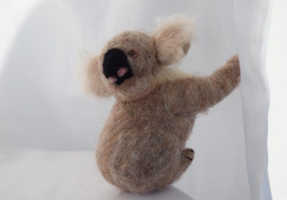 A felted Koala on a white background.