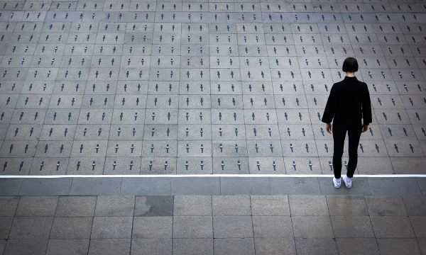 A woman dressed in a black top and trousers, and white trainers, stands with her back to us. In front of her are hundreds of watches laid equally spaced on the floor, two to each grey paving stone.
