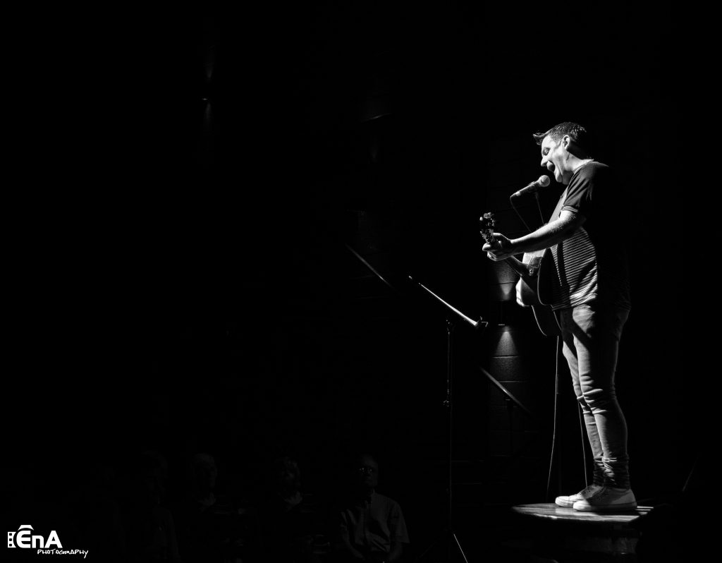 Black and White photo of Mike McGrother standing on a table in a dark room. He has a guitar and is singing into a microphone. by EnA Photography