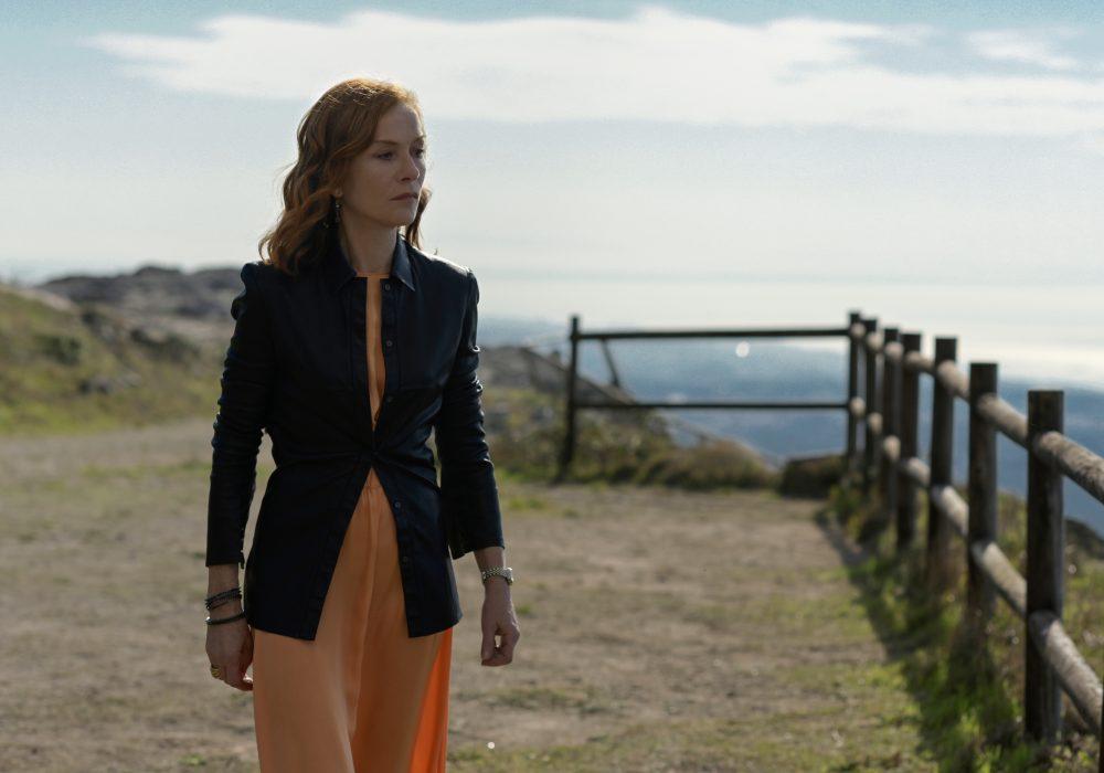 Woman stood on a dirt path near cliffs