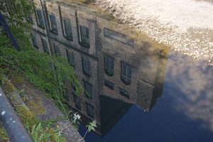 Photo of a building reflected in water.