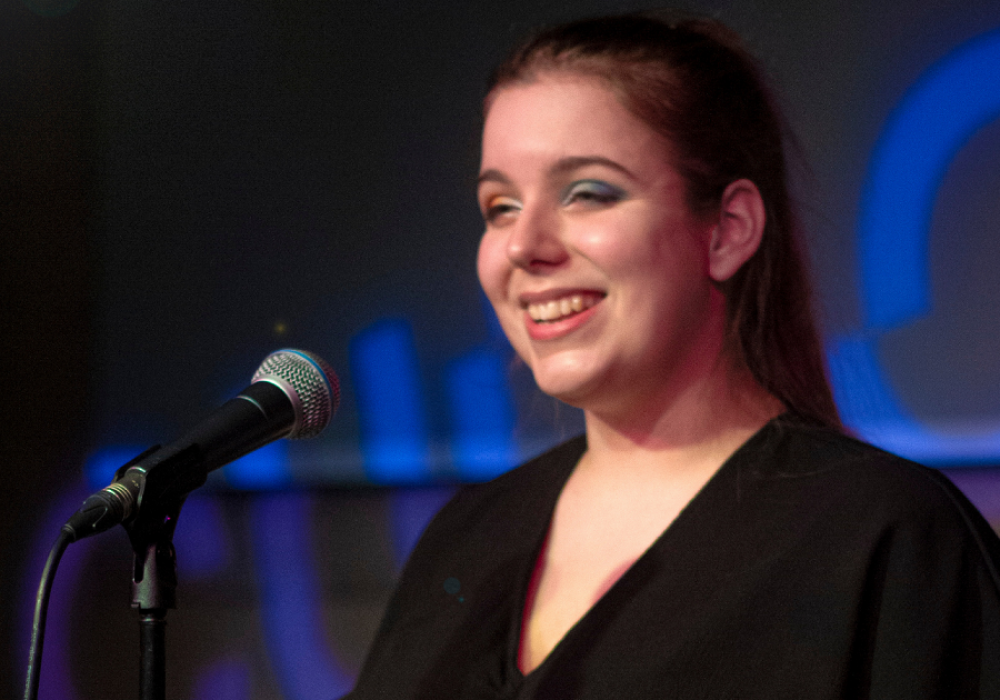 Image of artist Lizzie Lovejoy at a microphone, performing.