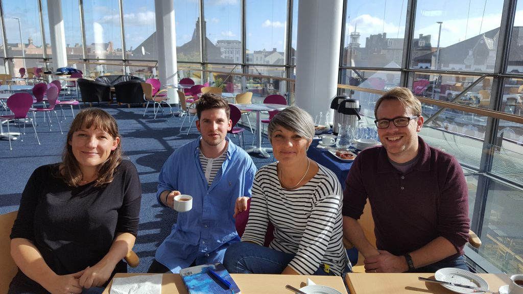 Four members of Fidget Theatre sitting at a table in ARC's second floor gallery space on a sunny day, with blue skies visible through the large curved glass windows behind them