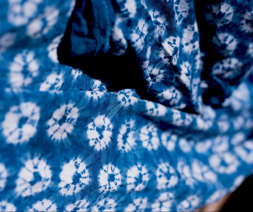 A piece of tie dyed cloth, it is dark blue with white circles