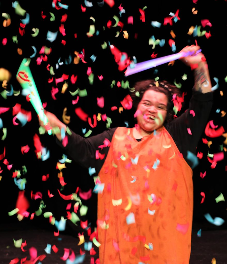 A person waving streamers with confetti falling around them