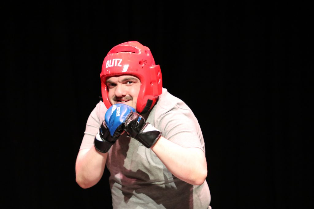 An actor in boxing gloves and helmet, in a boxing pose