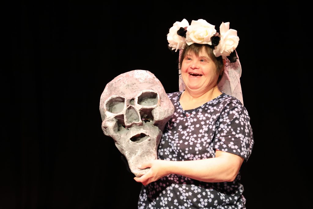 An actor wearing a flower crown holds an oversized skull
