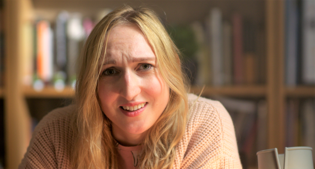 Actor Nicola Chegwin is pictured in a film still from Hen Night, playing the solo lead part of Jessica. Nicola is a young white woman with long blond hair. She is wearing a large oversized pale pink cardigan and pyjamas. She is seated at a desk which is out of shot, but we can see her crutch is leaning against it next to her. She is talking, and looking into the camera quizzically