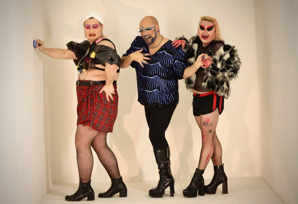Three drag artists in costume stand in a row and pose for the camera