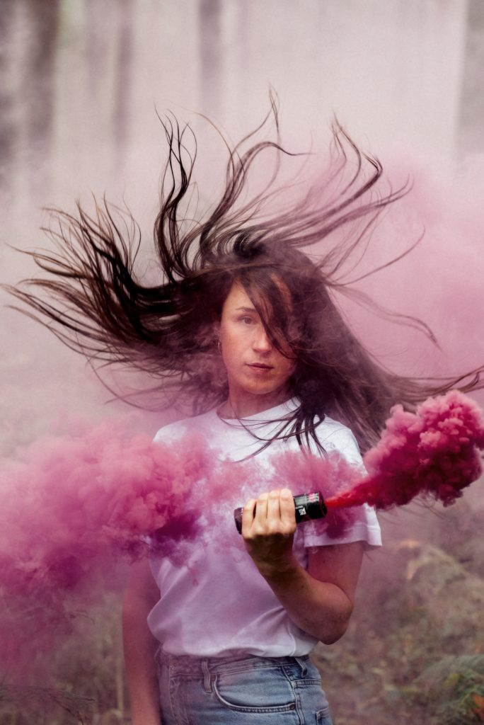 Luca stands facing the camera surrounded by pink smoke, and her long dark hair flying around her head